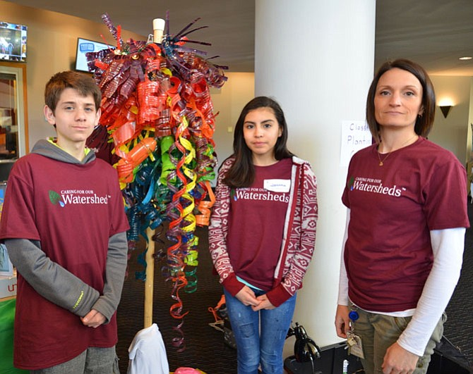 Even the Arts get in on the eco-friendly act. From left -- Lanier seventh-graders Aaron Harich and Jovanna Pineda were proud to display their chandelier, made over four weeks with about 150 recycled plastic water bottles, with the encouragement of Art teacher Kirby Kennedy.