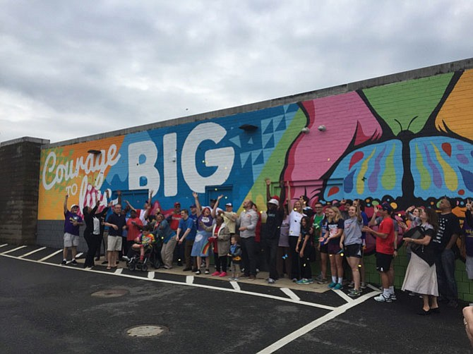 "The Miracle League Program celebrates the ""Live Big"" mural."