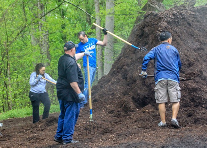 Volunteers tackle a mound of mulch. By the end of the event, they got it spread all around the parking lot and picnic areas.