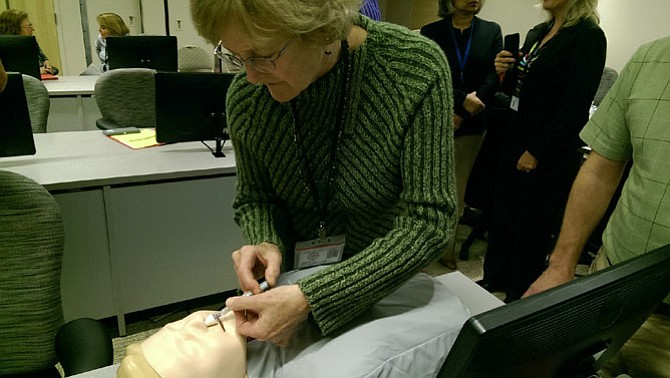 Cindy Koshatka, with Fairfax-Falls Church Community Services Board Emergency Services, practices administering a nasal spray of the overdose-reversing drug Naloxone.
