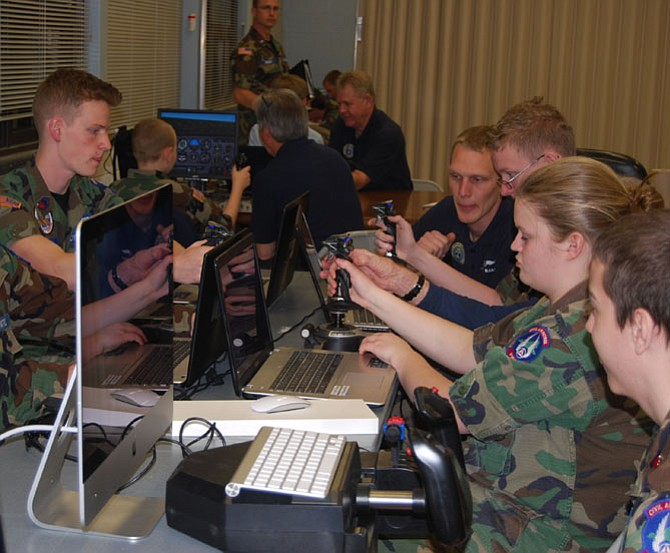 Civil Air Patrol (CAP) Senior Members and Cadets  from the Prince William and Burke Composite Squadrons concentrate at the controls of their flight simulators.