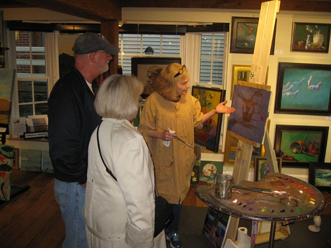 Artist Judith St. Ledger-Roty discusses her painting with guests at the First Friday Art Walk in the Village in Great Falls.