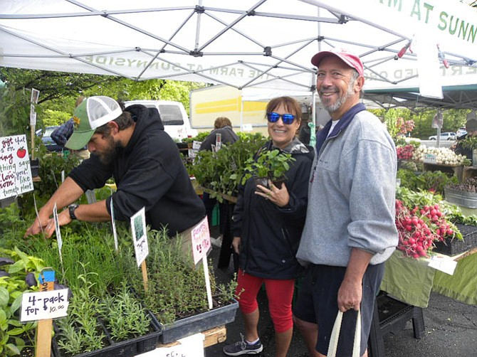 Casey Gustawarow (left) of The Farm at Sunnyside helps Allan and Barbara Ratner, of Reston, choose herbs on the opening day of the Reston Farmers Market on Saturday, May 7.
