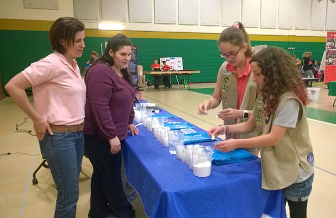 "From left -- Leaders Mary Nelson and Jessica Druetto of Troop 4914 in Burke-Springfield show 12-year-old Girl Scouts Annabelle Perry and Sarah Turner of Troop 2652 in Loudoun County how to ""make snow"" by using water to change the physical state of a sodium carbonate polymer."