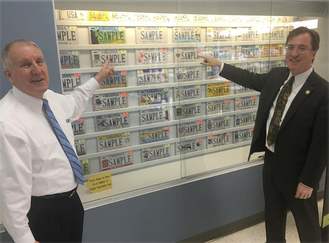 """DMV Commissioner Richard D. Holcomb and Del. Paul Krizek check out the license plate display at DMV's Lorton Customer Service Center. Krizek is pointing at the Family and Children's Trust Fund of Virginia's """"Kids First"""" plate. Krizek served as a volunteer trustee for eight years."""