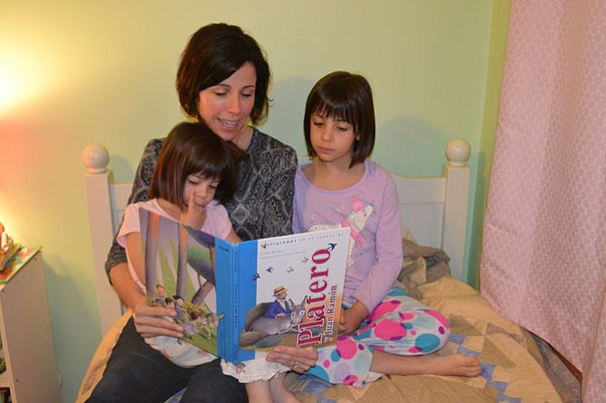 Martha Davis reads a book written in Spanish with her daughters, 6-year-old Alice (right) and 4-year old Jane. Alice is in a Spanish immersion program at Mt. Vernon Community School in Alexandria.