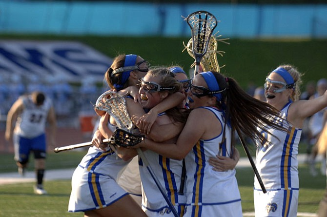 Members of the Robinson girls' lacrosse team celebrate their 13-11 victory over Langley in the 6A North region quarterfinals on May 19.