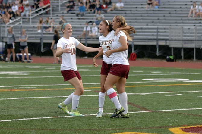 Oakton players (from left) Caitlin Violet, Alex Marquis and Alana Moore celebrate during the Cougars' 6A North quarterfinal game against Madison on May 26.