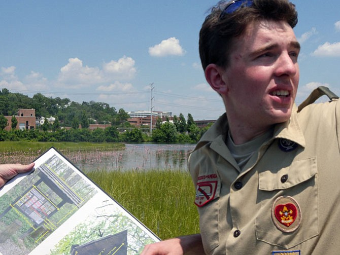 Thomas Pollack consults a diagram of the kiosk that he is supervising as his Eagle Scout project for Troop 135. He points to the top of the partially-finished kiosk where the roof will sit as the final step. The kiosk is located where the new Four Mile Run Wetlands Trail and Bike Trail meet in Four Mile Run Park.