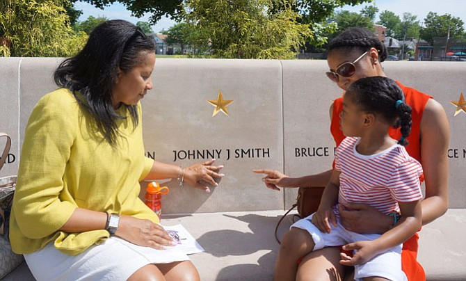 Arlisa Smith, left, sits by the name of her brother, Army Spc. Johnny Smith, with daughter Victoria Polite and granddaughter Brooke Robinson, 3,  prior to the start of the Memorial Day ceremony May 30 at the Capt. Rocky Versace Plaza and Vietnam Veterans Memorial.