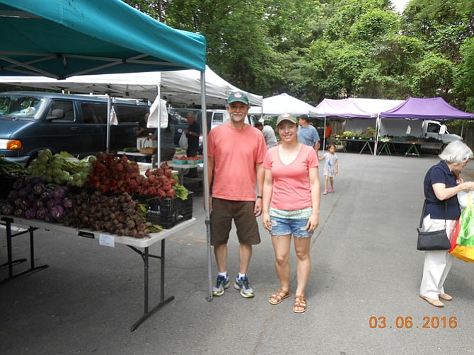 Farmers Market Manager Bob Baldwin and Market Coordinator Chelsea Roseberry near one vendor's produce section.