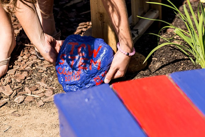 A ninth grade Minnie Howard student places a rock which they painted back in the garden. The painted rock was originally removed from the garden area when renovations began.
