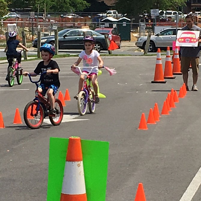 Two children practice their biking skills around the obstacle course set up by Vienna Parks and Recreation and monitored by Vienna police officers and volunteers.
