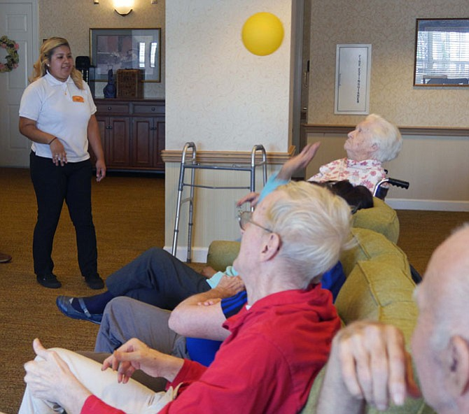 Jenny Bonilla tosses the balloon back and forth to residents in one of the favorite afternoon activities in Reminiscence at Sunrise of Alexandria. There are 33-34 residents in the Memory Care neighborhood for late stage dementia.