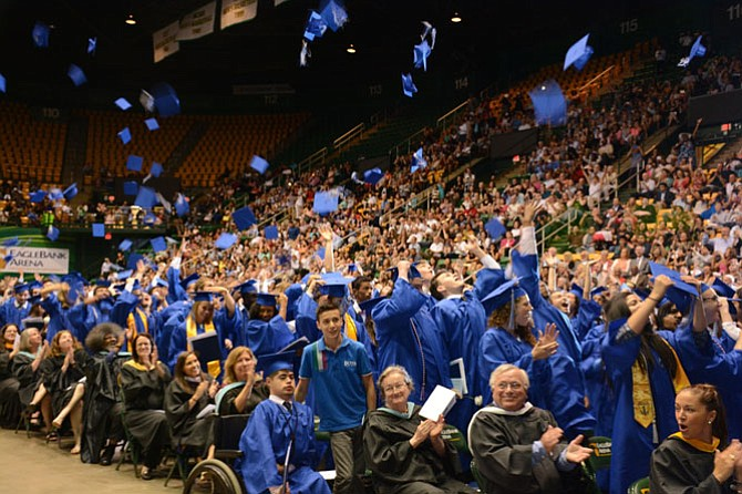 West Potomac High School class of 2016 graduates celebrate the turning of their tassels by hurling their mortarboards in the air.