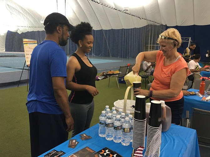 Bonnie Vona passes out refreshments at the Veterans Adaptive Players Clinic hosted by ThanksUSA at the Montgomery TennisPlex.