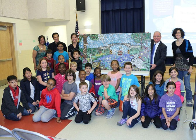 Students gather around their mural with (from left) Kaushika Patel, Seven Locks Elementary School PTA president; Arturo Ho, artist-in-residence; Dorothy Chung, Seven Locks Elementary School Educational Foundation President; Dr. James J. Virga, principal of Seven Locks Elementary School; and Adrienne Torrey, art teacher at Seven Locks Elementary School.