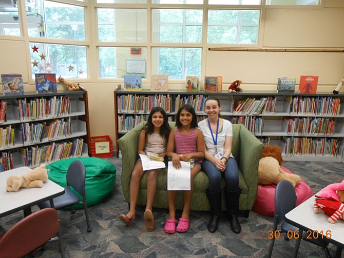 Nishka and Aanya in the children's reading area in the Great Falls Library with a librarian.