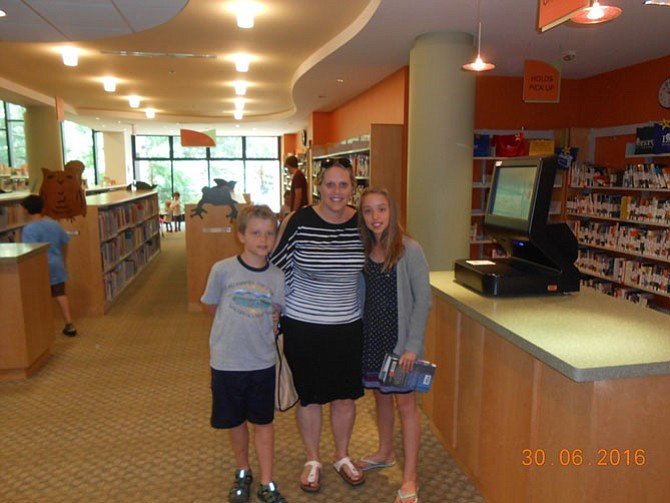 Stacey Smouse (center) and her two children, Hayden and Hannah, check out books for the Summer Reading Challenge.
