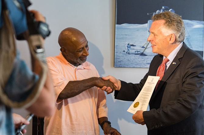 Gov. Terry McAuliffe (right) surprises Robert McNeil with his officially restored voter paperwork.