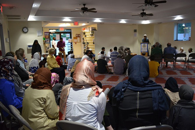 Members of the ICNA VA Islamic Center and additional community members listening to the mosque president, Rameez Abid, give a talk prior to iftar.