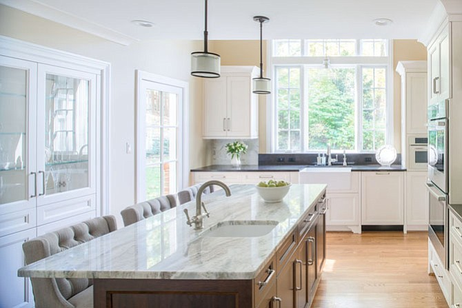 A large picture window is the focal point of this white kitchen by Anthony Wilder Design Build Inc.