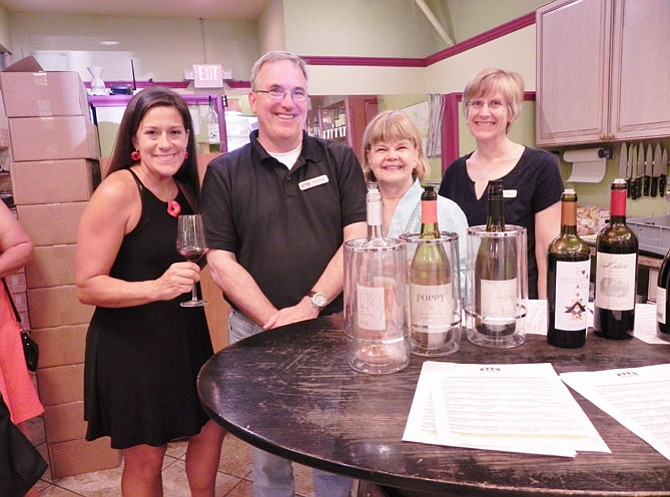 The chairman and co-chairman of the McLean Woman's Club's Holiday Homes tour pose with the  owners of Chain Bridge Cellars. From left: Michelle Arcari, co-chairman of the tour; Doug House, co-owner of Chain Bridge Cellars; Kathryn Mackensen, chairman of the tour; and Meg House, co-owner of Chain Bridge Cellars.