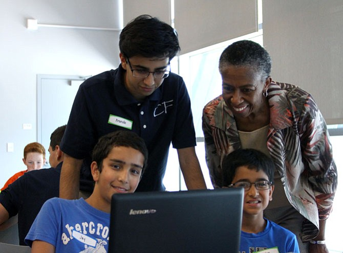 Students Jay Hemrajani, 11 (left), and Millen Chudasama, 10, show Pranab Krishnan and Supervisor Hudgins the code they were working on. The camp aimed to inspire creativity and innovation in science and technology.