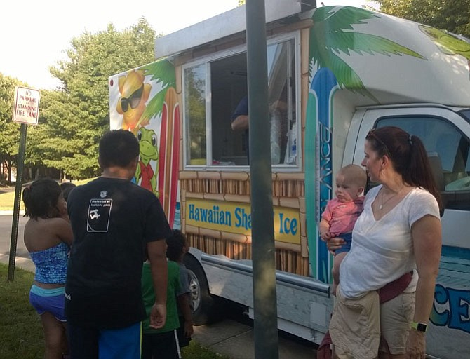 Anne Marie McCaskin, 37, holds her 24-month-old son, Toby, and watches their young neighbors line up for free shaved ice at a  National Night Out block party held Aug. 2 in the Random Hills townhouse community near Fairfax Corner.  She appreciates her local law enforcement agency and doesn't want her kids to be afraid to ask for help from police officers when they need it.
