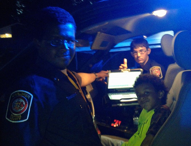 Yohannes Girma, 16, left, and his fellow Fairfax County Police Explorer Evan Hubbard, 15, let Noah Berhan, 7, check out a police cruiser — complete with all the bells and whistles, including a mobile office equipped with a computer-aided dispatch system at a Franconia District National Night Out block party Tuesday night in Alexandria's Bren Mar neighborhood.