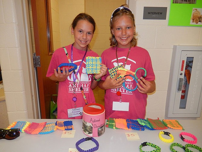 Shelby Mysel (left) and Tara Sankner hold their handmade potholders, dog collars and bracelets.