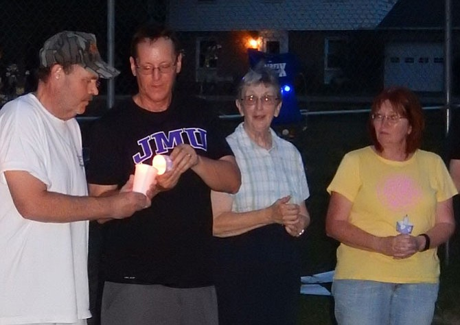 Lighting their candles are from left Jay Quade, Carey Cole, Pat Skeins and her daughter-in-law Debbie Skeins at the vigil.