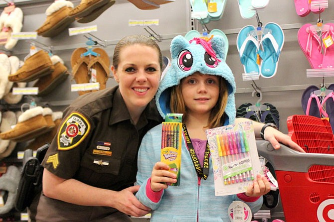 Sargent Emily Fary and Lily, 8, posing with the My Little Pony coat and the gel pens to replace the ones she missed having.