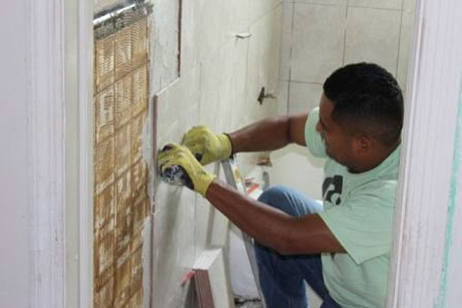 Eric Lopez, Community Lodgings' building engineer, replaces the bathroom tile as part of a complete bathroom renovation in a Community Lodgings affordable housing apartment.