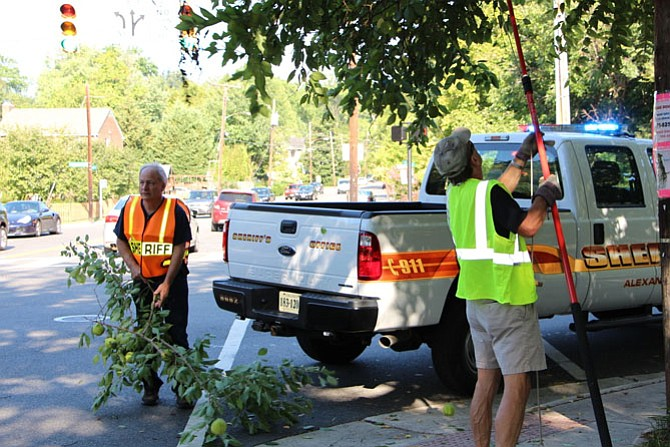 Sheriff Dana Lawhorne and a volunteer cut down branches that blocked the crosswalk signal at Commonwealth and Braddock.