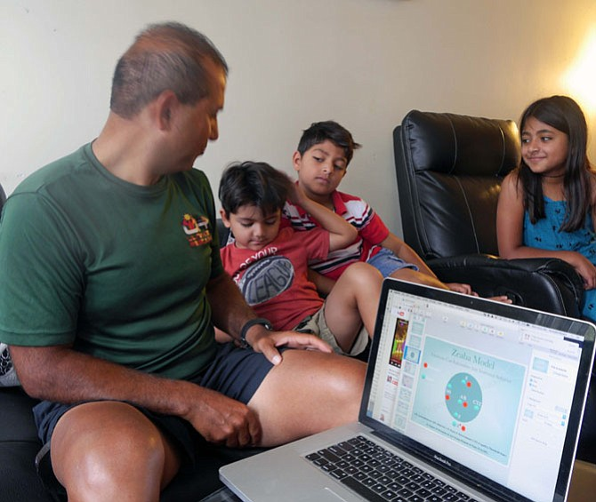 Mustafa Nazary, surrounded by three of his children, illustrates his behavioral model, Zeaba, named after his mom and his oldest daughter (right on couch.)