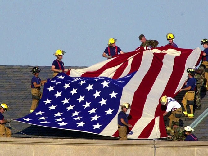Lt. Jim Morris, far bottom right, and fellow firefighters from Alexandria and Fairfax County Fire and Rescue Station 11 join soldiers atop the Pentagon to unfurl an American flag during rescue and recovery efforts Sept. 12, 2001. Morris's brother Seth died in the attacks on the World Trade Center.