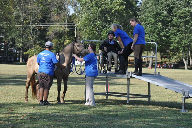 From left, Peter Colòn, Nicole Bass, Patti Towsley and Sarah Maceyak assist César Dulanto in mounting a horse at the 2015 Northern Virginia Therapeutic Riding Program Ride to Thrive fundraiser.