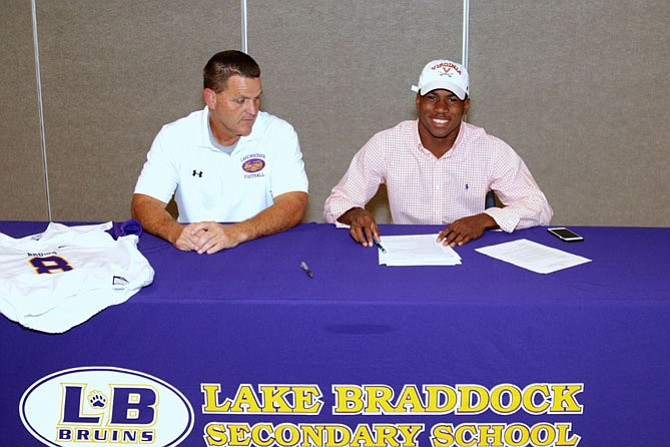 Lamont Atkins, of Burke,  signed his grant-in-aid scholarship package to play football for the University of Virginia. He is joined by his coach Jim Poythress, Lake Braddock's Varsity Football Head Coach.