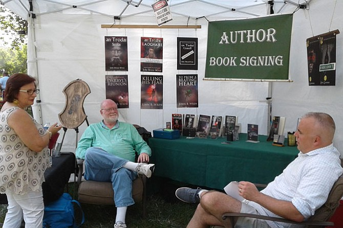 Burke jeweler and tour guide Olya Yampolsky visits Fairfax County novelists John B. Wren and Eric Gardner Sept. 10 in their booth at the annual Burke Centre Festival.