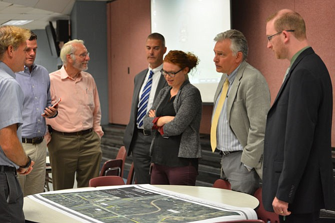 Kristin Calkins with  Fairfax County Department of Transportation (FCDOT) and other officials from the department review some of the maps and talk about the proposed improvements to Hunter Mill Road with members of the community at their latest informational outreach meeting.