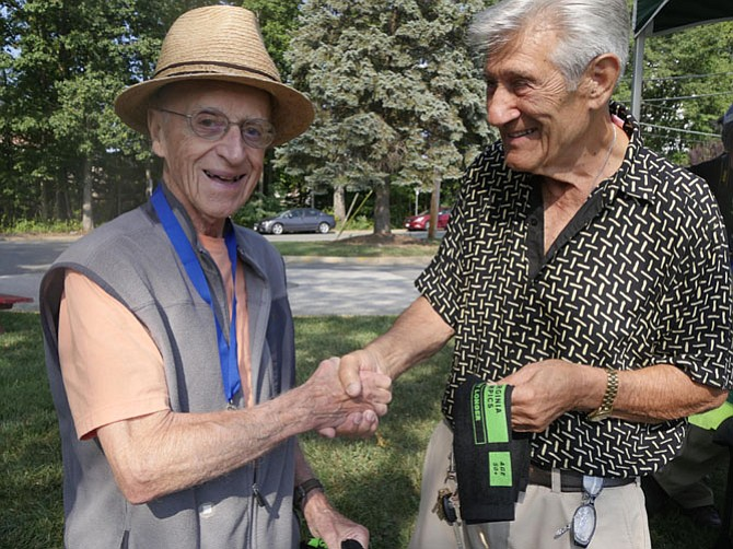 "Nicholas Garito, Fairfax, shakes hands with his regular league bocce partner Henry Coletto after Coletto completes his bocce match in the 90-year old plus category in the Senior Olympics on Sept. 15. Garito says, ""Henry turned 91 two weeks ago and instead of a cake I decided to celebrate with Oh Henry candy bars. I had to look all over to find them."" Colette says he put his in the freezer for the future. After the match they watch the other players and reminisce about the wars — World War II for Colette and Korean War for Garito."