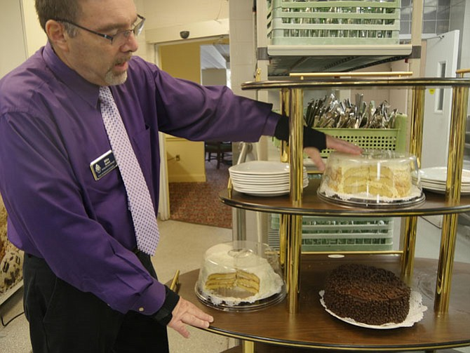 Mike Solari, the purchasing and catering manager at Vinson Hall, readies the dessert cart for lunch with coconut cake, chocolate mousse and lemon cakes. Soon it will be full of tarts and other choices offered in the formal dining room.
