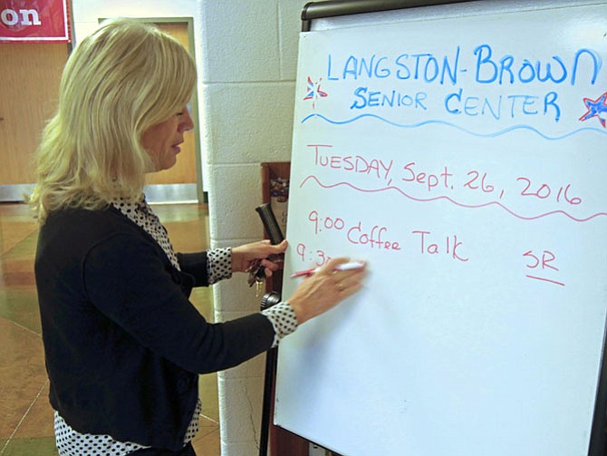 "Elizabeth Poole, director of the Senior Center at Langston-Brown Community Center, is writing the day's activities on the board outside the center. She says every day includes a hot lunch, as well as activities, sometimes special speakers and field trips. She says the seniors sometimes suggest new classes such as ""yarn creation"" that began with 3-4 people and has grown to 6-9 attendees. Another popular activity is the choral group of 50-60 who meets weekly and performs winter and spring concerts."