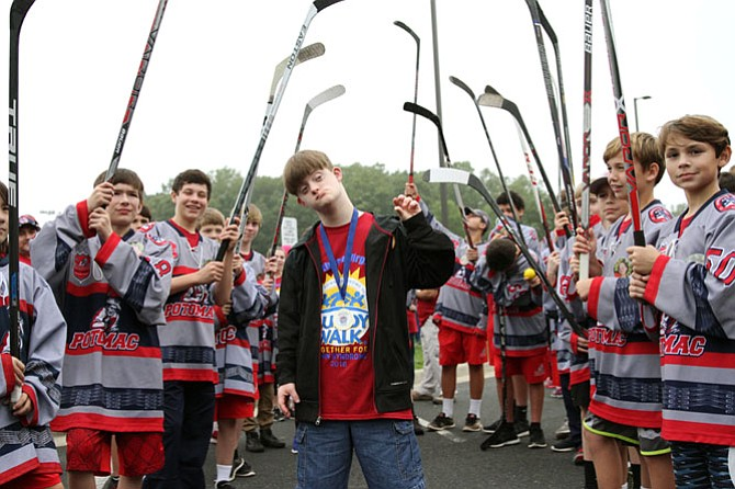 Tanner Kerby, 17, from Warrenton stands with members of Potomac Patriots Hockey after receiving a medal from them upon completion of the Buddy Walk.