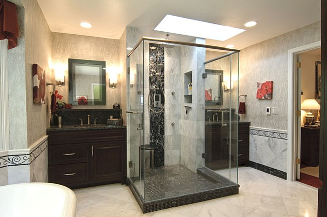 A glass enclosed walk-in shower accessible from two sides is tucked under a skylight.