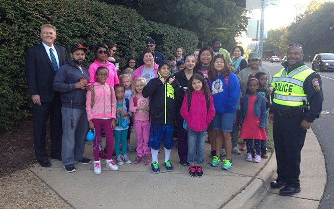(Left) Supervisor John Cook (R-Braddock) and (right) West Springfield District police station commander Capt. Gervais Reed meets with students and parents on their way to Terra Centre Elementary School on International Walk to School Day, Oct. 5, 2016.