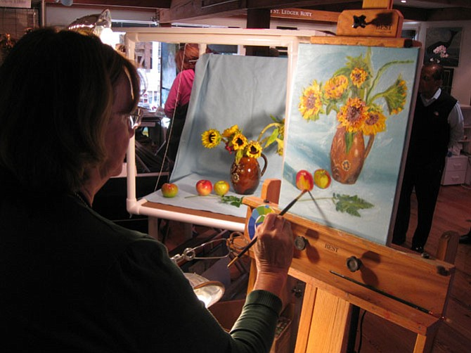 Carol Howard with her piece, Sunflowers, at The Artists' Atelier in the Village Green.