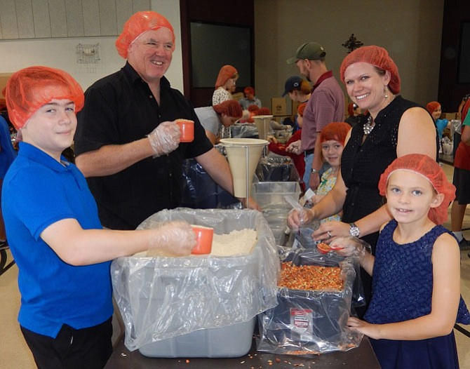 Measuring food for the meal packets are (from left) Brian Hesse, 11; Dwane Evans; Janie Hesse, 7; Johannah Evans and Samantha Evans, 7.