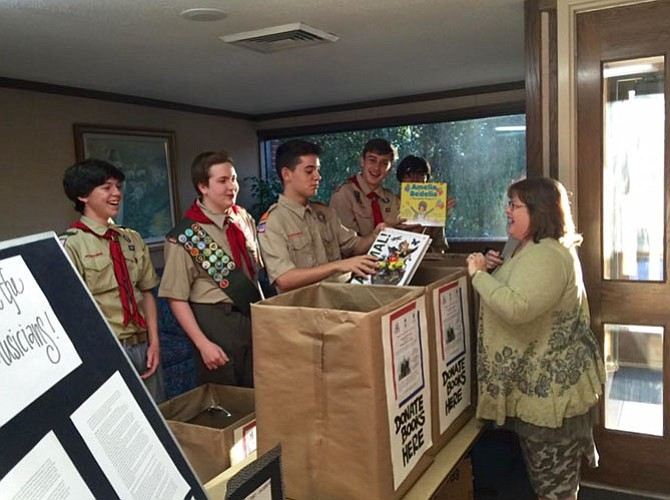 Scouts collecting books at door.